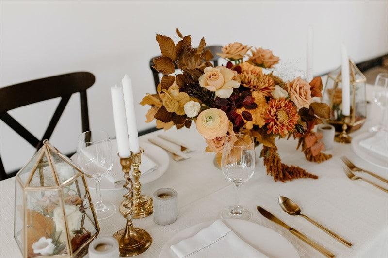 Mesa com pratos e talheres, e como decoração velas e flores
