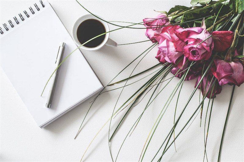 Agenda com uma caneta, e uma xícara de café e rosas ao lado