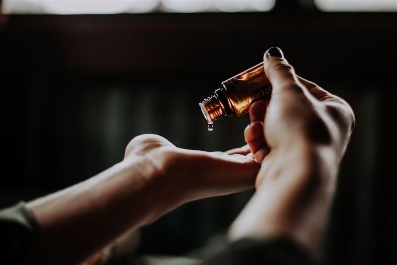 Imagem de uma pessoa pingando óleo essencial nas mãos